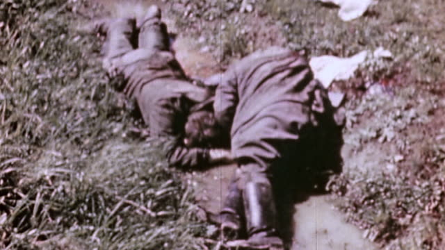 German Army and civilian casualties lying in field wounded soldiers tossing and moving a pile of casualties and a grave digger working / Czech...