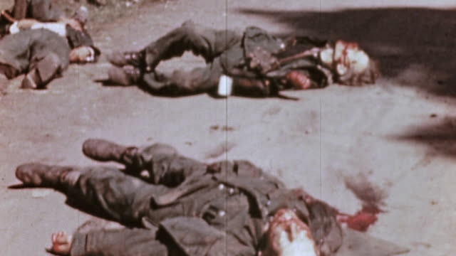 German Army casualties with bloody faces lying on road and fallen into nearby ditch / Czech Republic