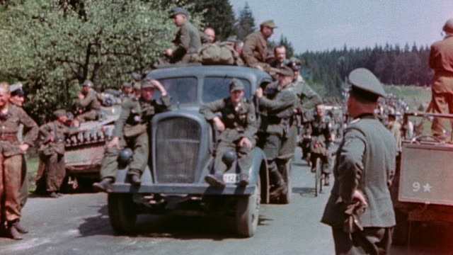 vidéos et rushes de german army officer returning nazi salute as truckload of surrendering soldiers drive past bicyclist hanging on to the fender - armée allemande