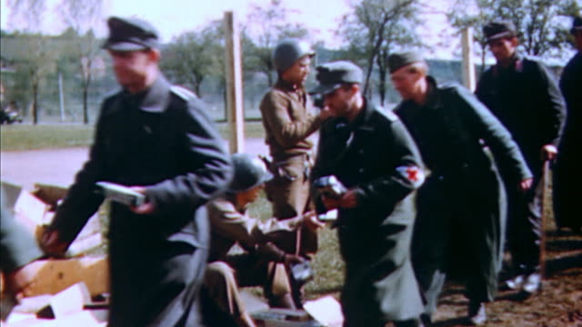 german army pows in a long line for krations handed to them by us army soldiers / germany - wehrmacht stock-videos und b-roll-filmmaterial