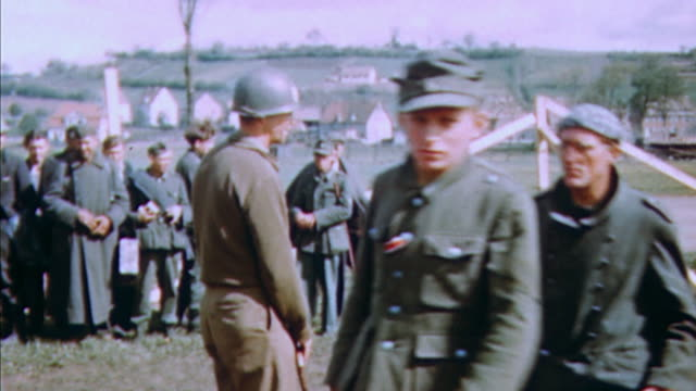 German Army POWs marching in long line with US Army MP selecting some and pulling them out of queue / Germany