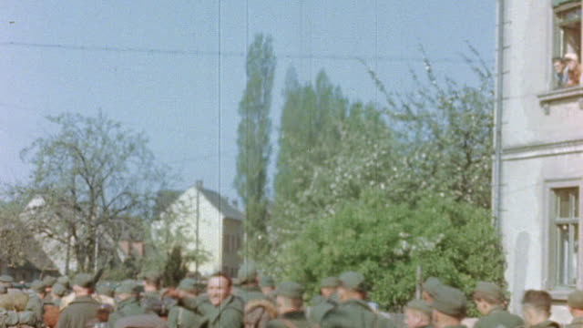 German Army prisoners of war carrying their belongings marching through a village street escorted by US Army soldiers and liberated French prisoners...