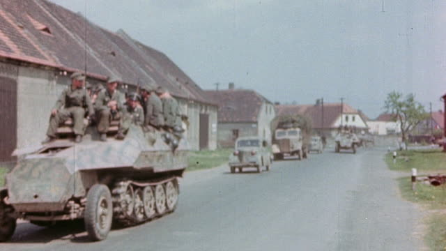 vídeos de stock, filmes e b-roll de ha german army soldiers in halftrack armored personnel carrier driving down street followed by staff car - wehrmacht