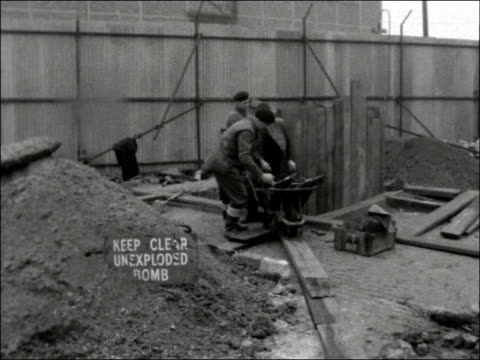 german bomb unearthed at surrey docks; england: london: surrey docks: ext gv site where bomb found with workmen about and cranes in b/g / top shot of... - manual worker stock videos & royalty-free footage