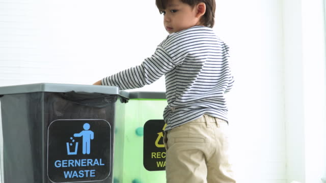 german boys seperate plastic bottle into recyclable bin - ease stock videos & royalty-free footage