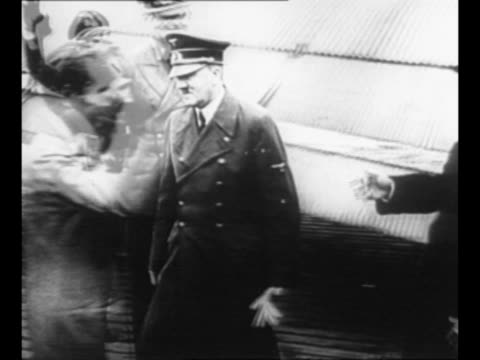 german chancellor adolf hitler in uniform and former italian dictator benito mussolini in mufti shake hands as mussolini deplanes after escaping from... - ベニート ムッソリーニ点の映像素材/bロール