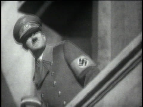 german chancellor adolf hitler stands on a balcony watching nazi soldiers march by carrying torches. - deutsches militär stock-videos und b-roll-filmmaterial