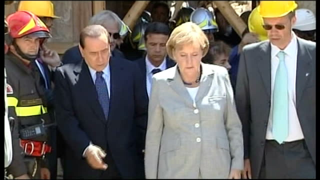 ext german chancellor angela merkel being given tour by italian prime minister silvio berlusconi of earthquake zone and berlusconi shaking hands with... - terremoto video stock e b–roll