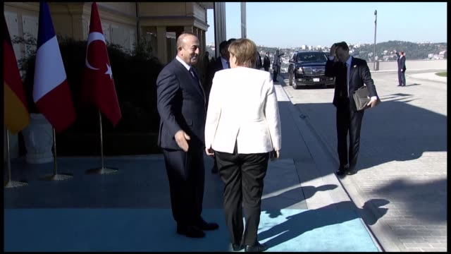 german chancellor angela merkel is welcomed by turkish foreign minister mevlut cavusoglu as she arrives at vahdettin pavilion for the 4way syria... - syrien stock-videos und b-roll-filmmaterial