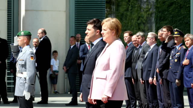 german chancellor angela merkel listens to the ukraine national anthem as she stands on a hot day with new ukrainian president volodymyr zelensky... - アンゲラ・メルケル点の映像素材/bロール