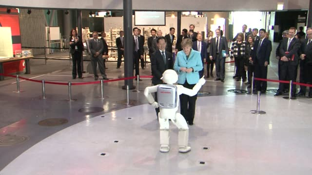 German Chancellor Angela Merkel makes friends with a disco dancing pogo ing and football playing android robot during her visit to Japan