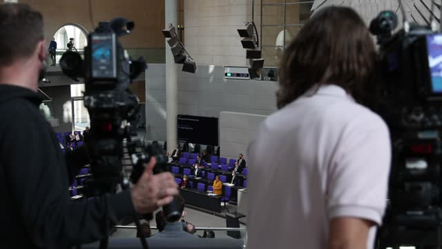 vidéos et rushes de german chancellor angela merkel takes questions from parliamentarians at the bundestag after she announced a reversal of a hard lockdown for easter... - caméraman