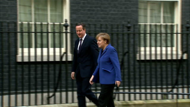 German Chancellor arrival in Downing Street ENGLAND London Downing Srteet EXT Car along past camera operators and press / Angela Merkel getting out...