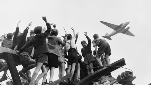 german children cheer for a united states cargo airplane from atop  a heap of rubble during the berlin airlift. - 1948 stock videos and b-roll footage