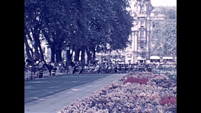 german civillians stroll among trees and flowers and enjoy sitting on park benches people walking inside a grand white columned structure just weeks... - 1939 stock-videos und b-roll-filmmaterial