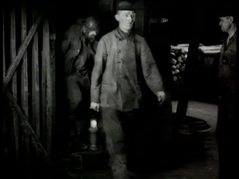 german coal miners w/ lamps walking out of coal mine miner at store counter w/ bottle of schnapps collecting cigarette packs ruhr valley - minatore video stock e b–roll