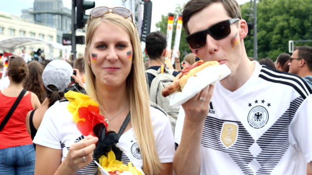 german couple are eating a curry sausage and fries during the 2018 fifa world cup match between germany and south korea at the fan mile public... - 飲食点の映像素材/bロール