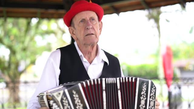 vídeos y material grabado en eventos de stock de pendiente alemana senior hombre tocar acordeón en blumenau, santa catarina, brasil - acordeonista