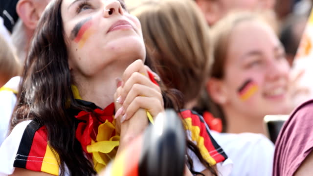 German female fan with the german flag colors on her cheeks is praying while Germany is loosing the 2018 FIFA World Cup Russia Group F match against...