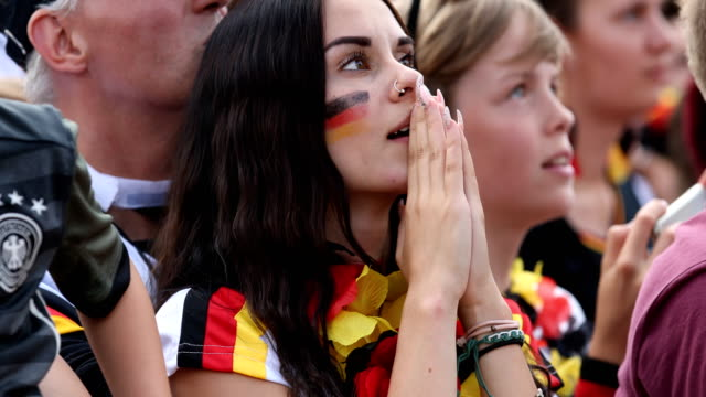 German female with the german flag colors on her cheeks is praying while Germany is lossing the 2018 FIFA World Cup Russia Group F match against...