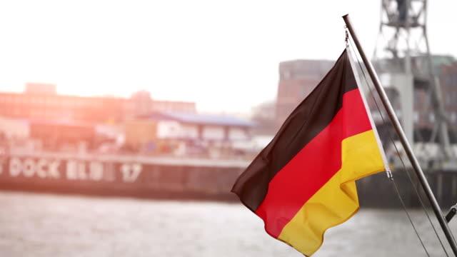 stockvideo's en b-roll-footage met german flag at the harbor of hamburg and elbe river - kleurtoon