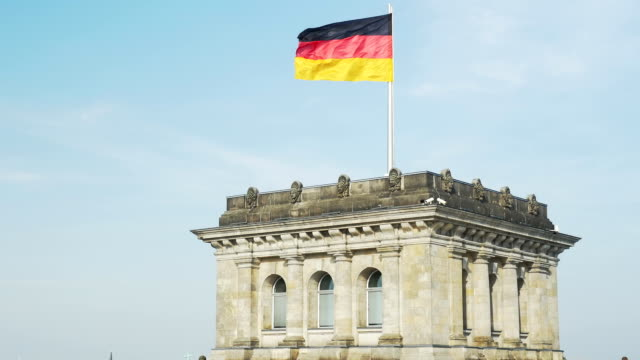 german flag blowing on reichstag building (4k/uhd to hd) - german flag stock videos & royalty-free footage