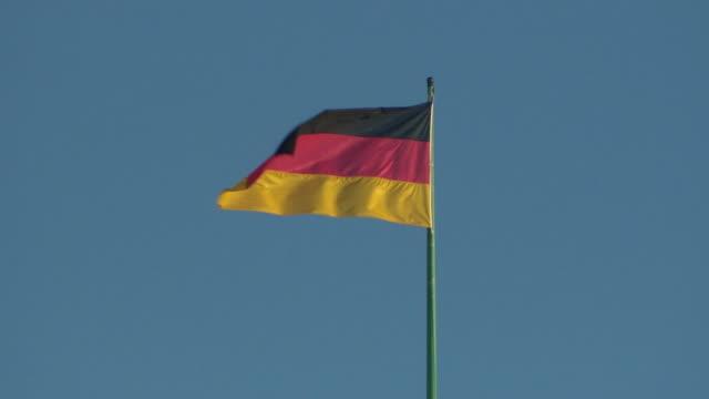 German flag flying against clear blue sky in Berlin