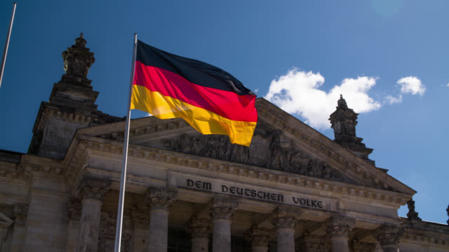 german flag in front of reichstag building, berlin - german flag stock videos & royalty-free footage