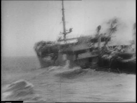 german freighter in distance / german pows loaded from rubber raft to us boat / us battleship releases torpedo and depth charges / german ship is hit... - torpedo stock videos & royalty-free footage