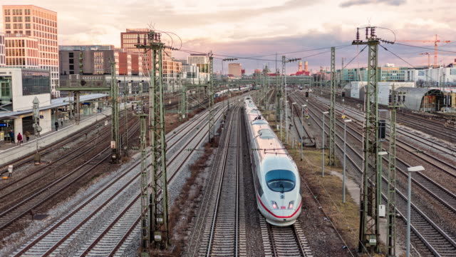 German ICE Inter City Express and regional trains - time lapse footage of leaving and arriving trains shot off a bridge while day with dramatic sky and clouds - trains leaving to Berlin