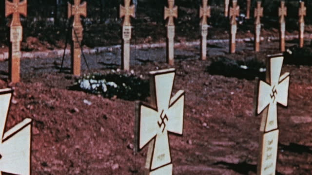 pan german military cemetery grave markers shaped like the iron cross and swastikas painted in the middle / germany - grab stock-videos und b-roll-filmmaterial
