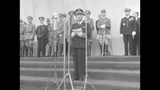 vídeos y material grabado en eventos de stock de german naval officer standing on steps behind microphones reading from papers in hands, german officers and french officials stand against wall... - fascismo