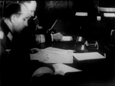 German Nazi General Alfred Jodl at table signing paper VS Allied officers at signing General George C Marshall FG table Standing Lieutenant General...