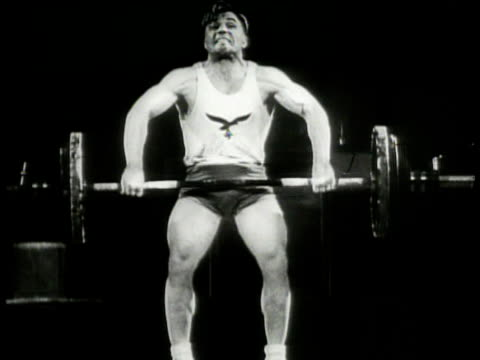 vídeos de stock, filmes e b-roll de german nazi male weightlifter in luftwaffe tee shirt on stage attempting 'snatch' lift lifting barbells from floor amp overhead in one move not able... - levantamento de peso