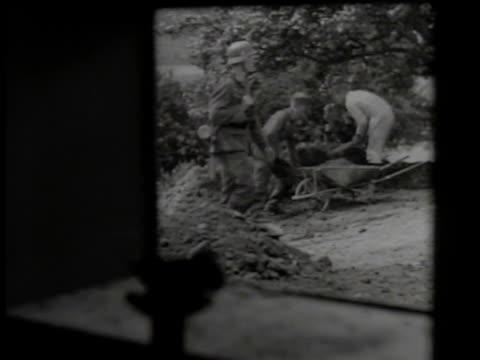 german nazi officer in coastline fortification looking through large, mounted binoculars. german soldier walking by workers digging, using pick axe.... - coastal feature stock videos & royalty-free footage