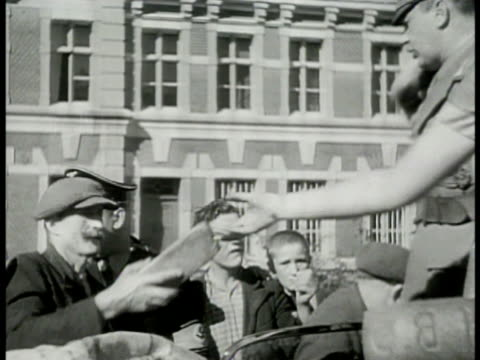 vidéos et rushes de german nazi soldiers outdoors handing out loaves of bread to civilians german nazi soldiers placing small food bags in elder woman's outstretched... - 1942