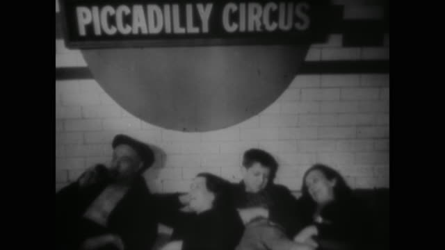wwii german planes drop bombs as the people of london sit in makeshift air raid shelters in the underground railway system - 防空壕点の映像素材/bロール
