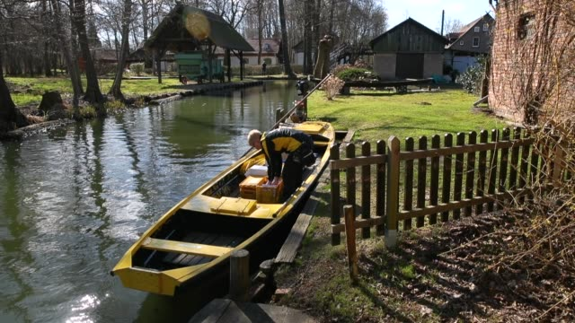 german postal carrier deutsche post postal worker andrea bunar guides her flatbottomed canoe as she delivers the mail in the web of canals in the... - postangestellter stock-videos und b-roll-filmmaterial