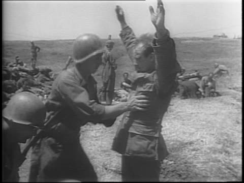 german prisoners are marched under allied guard / german soldiers surrendering / pows entering a barbed wire gated pen / building wreckage along... - arrendersi video stock e b–roll