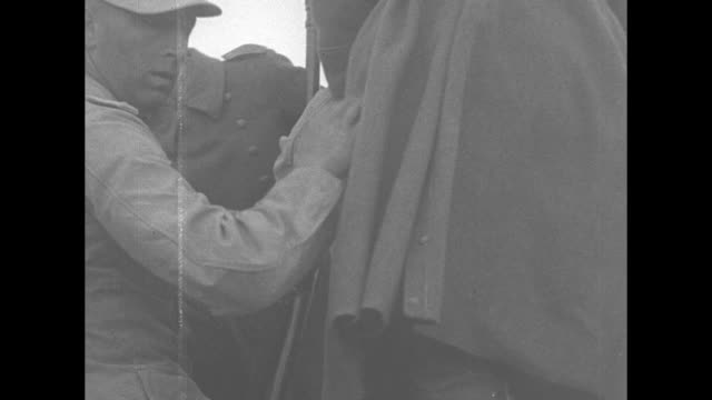 VS German prisoners in the desert men climbing on back of truck a surrendering German with upraised hands stops in front of a tank the search him...
