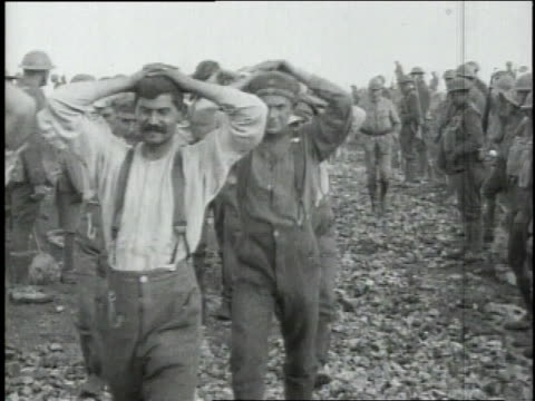 German prisoners of war with hands above their heads being marched along road that is under construction / Boureuilles Lorraine France