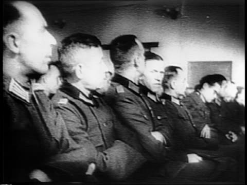 german prisoners seated in hall / closer view of officials from national committee for free germany at table on dais / speakers urge nazi soldiers to... - nazi germany stock videos and b-roll footage