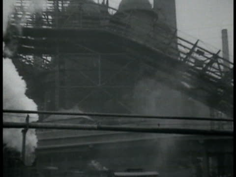 stockvideo's en b-roll-footage met german saar steel mills working smoke stacks standing in fog train station load area molten steel being poured into vat w/ sparks flying. - nazism