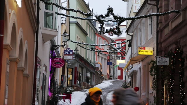 German shopping strip during the holidays, tilt down with snow