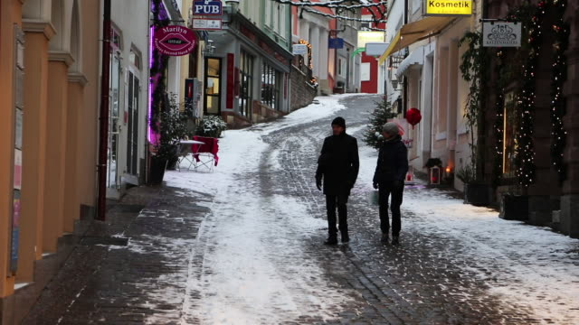 stockvideo's en b-roll-footage met german shopping strip during the holidays, tilt up with snow - winkelbord