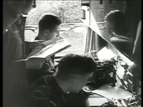 german soldier reading orders on paper, another soldier typing on typewriter. pole w/ extending wires. german soldiers in open vehicle w/ radio,... - 1939 stock-videos und b-roll-filmmaterial