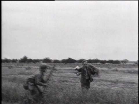 vidéos et rushes de german soldier with hands up, running toward armed soldier / soldier searching man / soldier removing helmet from captured german soldier, a teenaged... - 1944