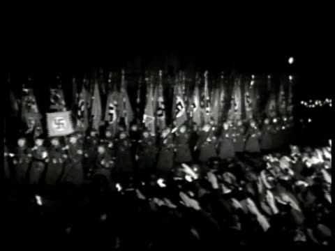 GERMANY NIGHT German soldiers carry Nazi flag banners people in crowd saluting w/ arms extended Troops marching in street w/ torches INT XWS Nazi...