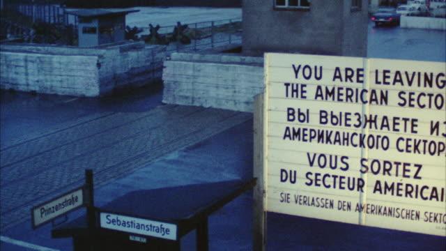 stockvideo's en b-roll-footage met 1966 ws tu zi german soldiers crossing street, berlin wall and guard post at dusk / berlin, germany - berlijnse muur