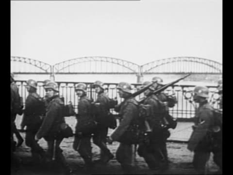 vídeos de stock e filmes b-roll de german soldiers march in steel helmets in warsaw after germany's invasion of poland / warsaw citizens stand on side of street watch / soldiers march... - 1939